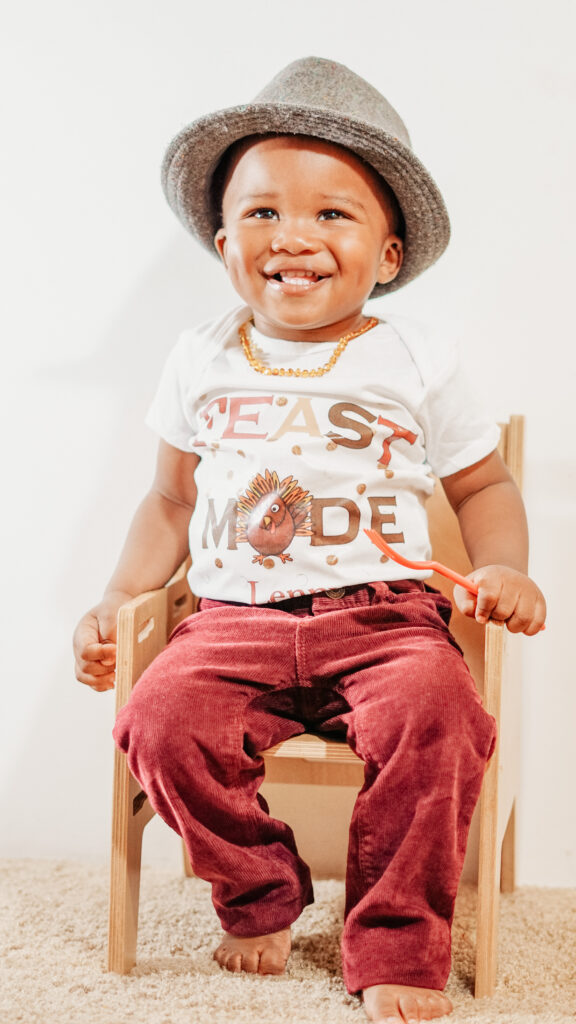 """In the picture is Brittany's toddler son, Lennox holding a fork, wearing a hat, sitting in a chair and wearing a shirt that says """"Feast Mode."""""""