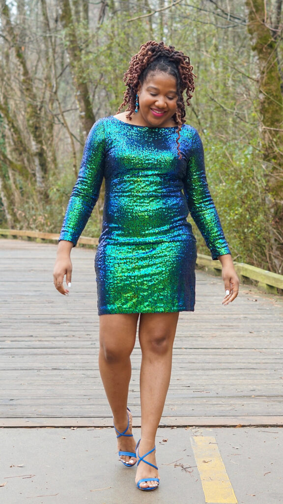 Brittany is walking in a sparkly green and blue dress.