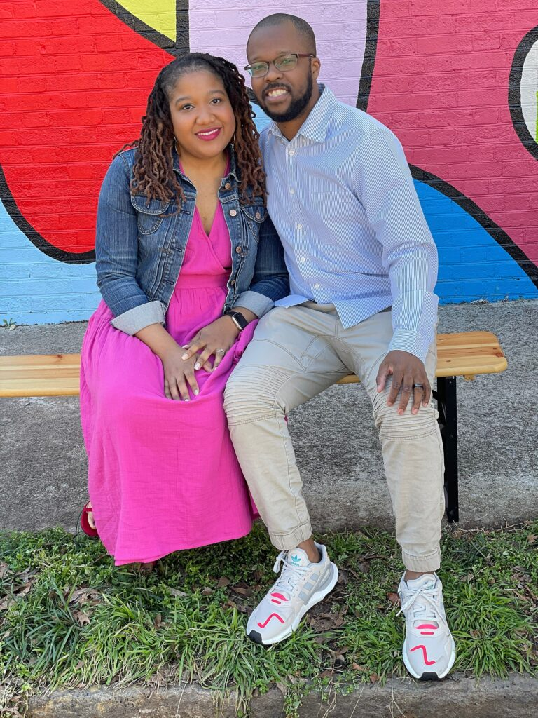 Brittany and Anthony are sitting on a bench in front of a mural. They are smiling, Anthony has his arm around Brittany and Brittany's hands are in her lap.