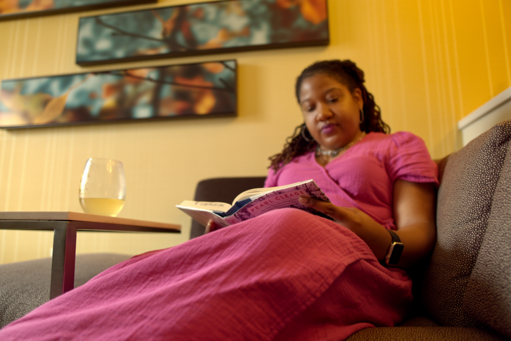 Brittany in sitting on the couch of her hotel room looking down as she reads a Pearl Cleage book.