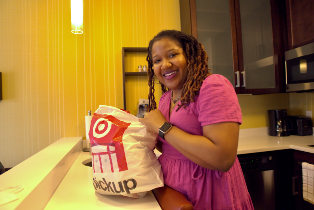 Brittany is smiling in the kitchen of her hotel room. She is holding a Target bag in her hand.
