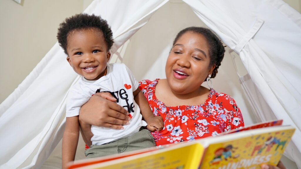 """Brittany is holding Lennox while sitting in his tent bed. She is reading the book """"Kindness Makes Us Strong"""" and Lennox is smiling at the camera."""