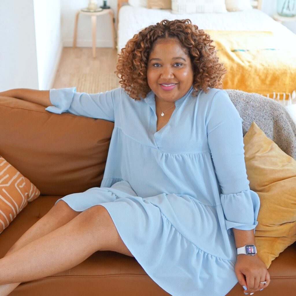 Brittany is wearing a crocheted curly hairstyle in a blue dress. She is sitting on a couch smiling at the camera.
