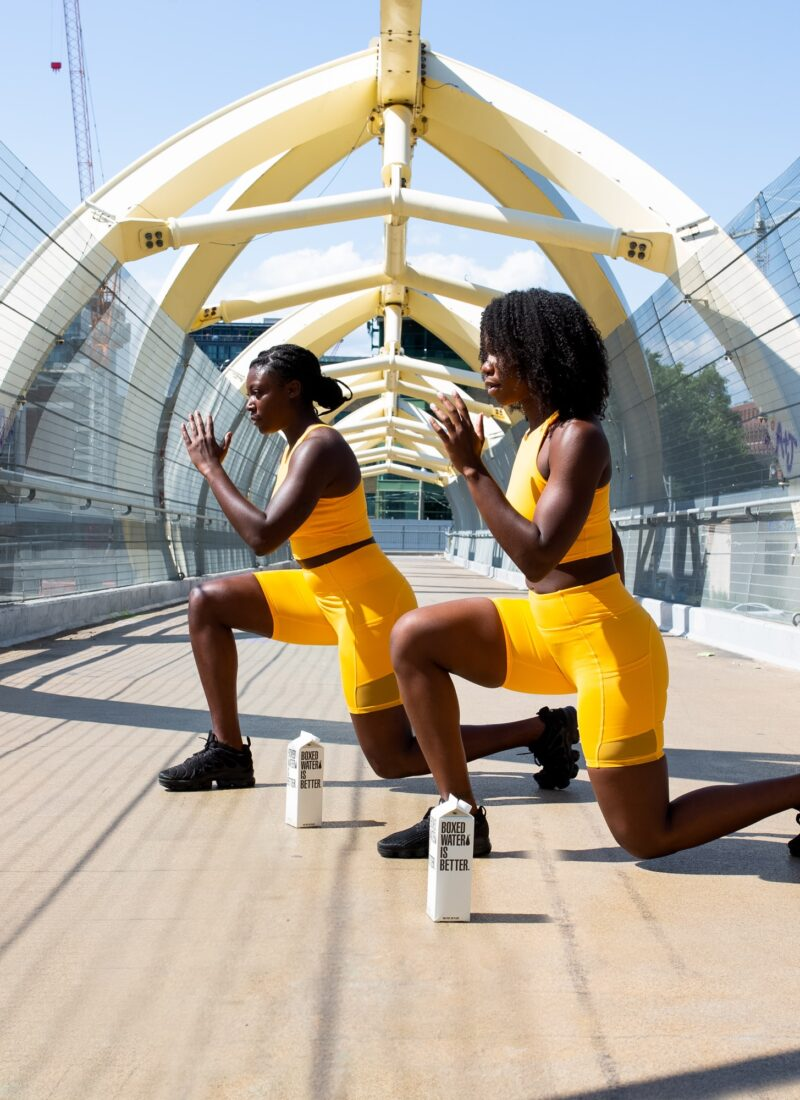 This image shows two black women stretching in yellow exercise apparel.