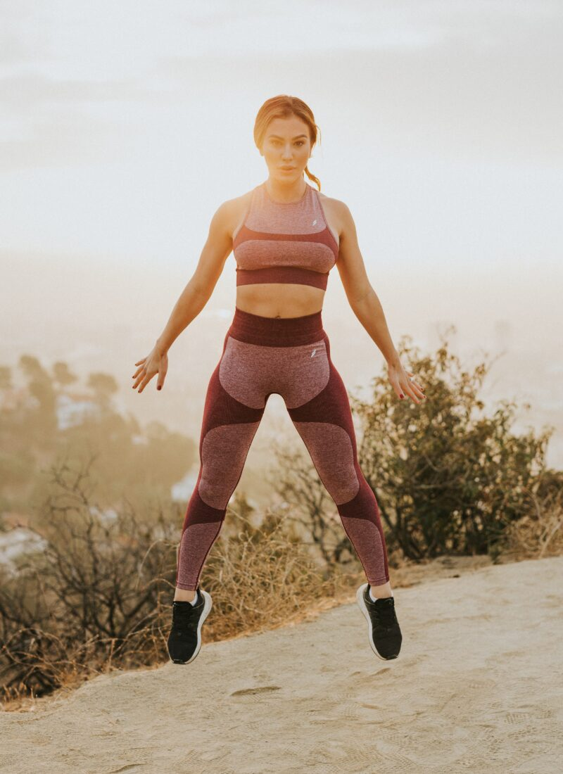 This photo shows a woman jumping while wearing exercise leggings and a tank.