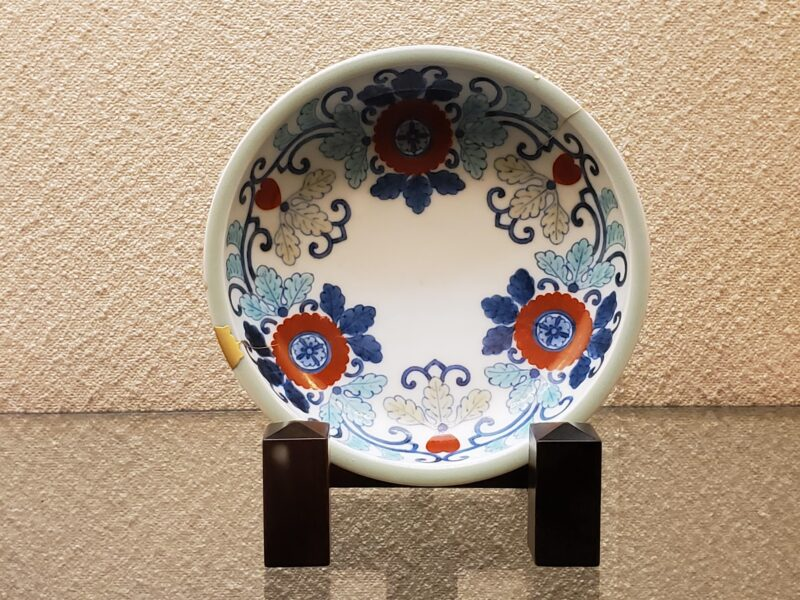 Тарелка с многоцветной надглазурной росписью ироэ и узором из цветов в китайском стиле. Получила лишь едва заметное селадоновое глазурирование по ободу (конец 17 в)
