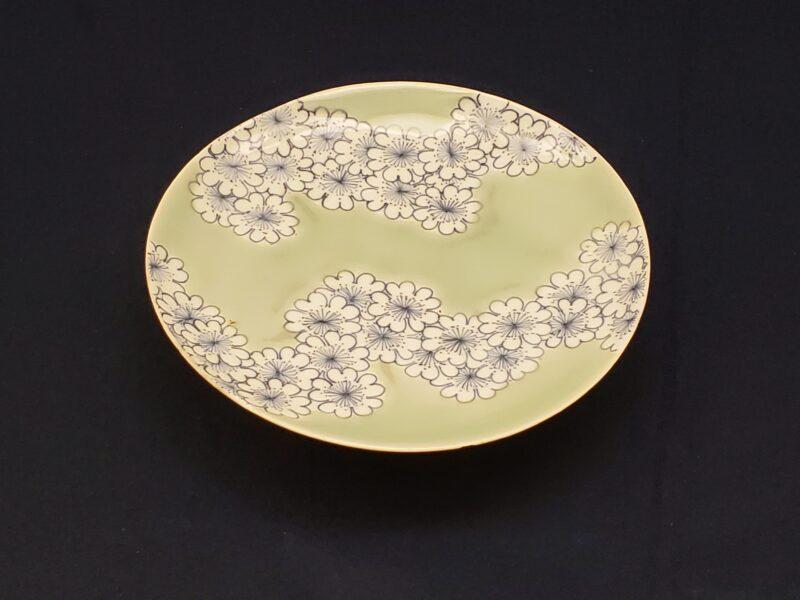 Тарелка сомэцукэ-сэйдзи с цветками сакуры, выполненная с применением техники какэвакэ (конец 17 в). Динамично отображенные грозди цветков вишни на тёплом селадоновом фоне при всем своем минимализме создают законченный сюжет, типичный для стиля Набэсима