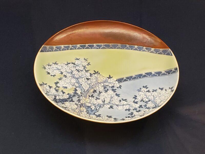 Тарелка саби-сомэцукэ-сэйдзи, сочетающая три различных эмали: красно-коричневую, селадоновую и прозрачную поверх кобальтового рисунка вишни на белом фоне (конец 17 в)