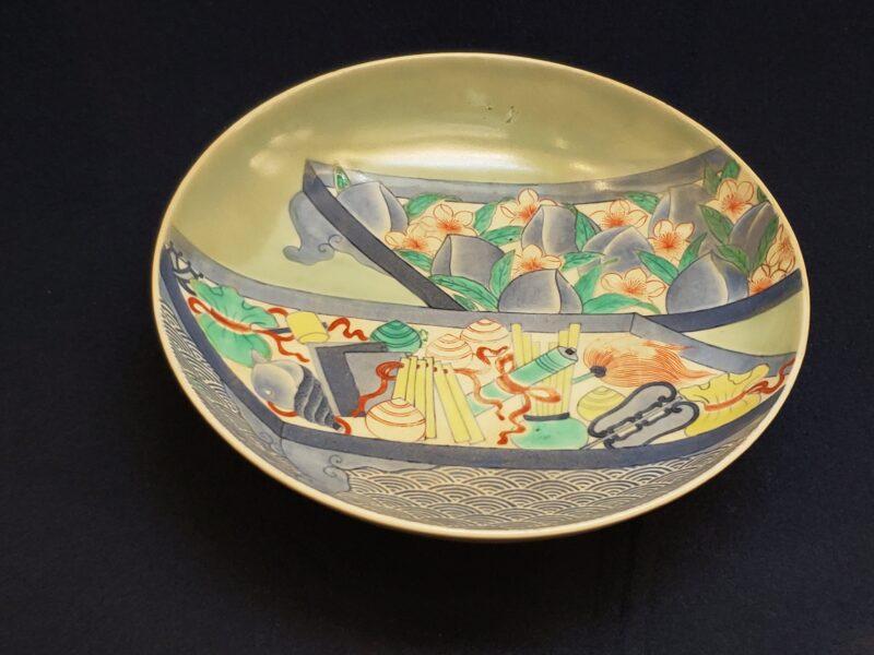 Тарелка, изображающие подносы с персиками и праздничными украшениями. Сочетание техник раздельного нанесения глазури, суми-хадзики и многоцветной надглазурной росписи (конец 17 в)