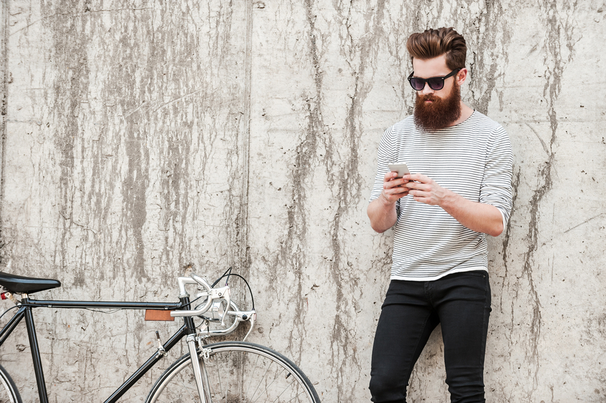 Handsome young bearded man holding mobile phone while standing near his bicycle against the concrete wall