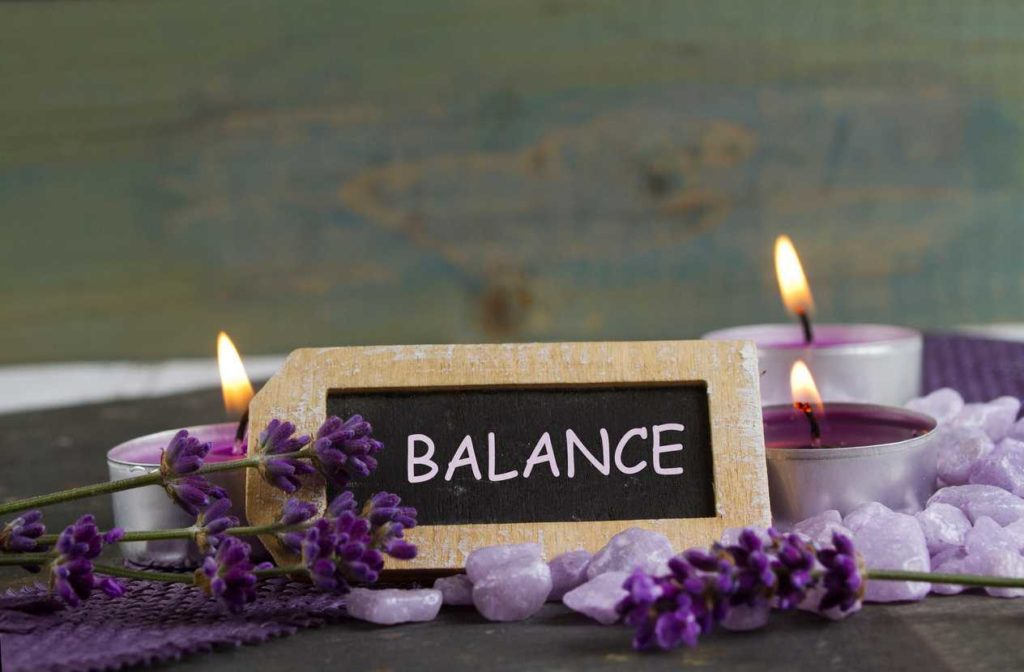 Blackboard that says balance with one candle on each side