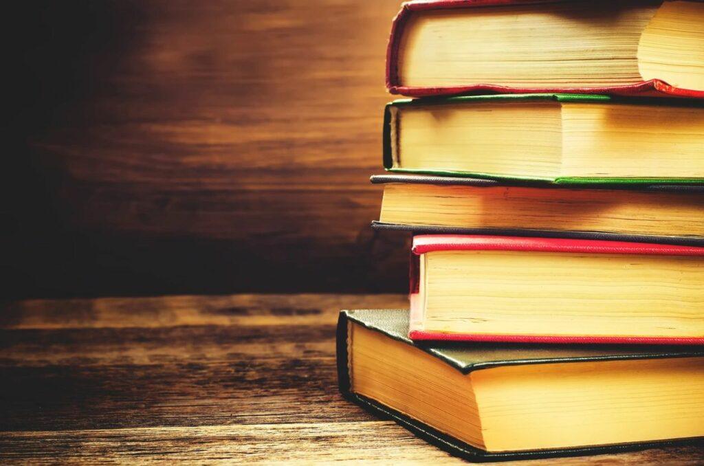 5 novels in a pile on a wooden desk