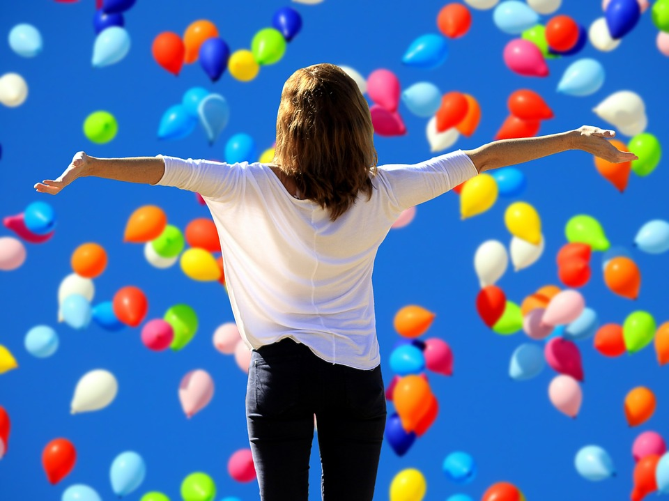 girl spreading arms out as colorful balloons fly in the sky
