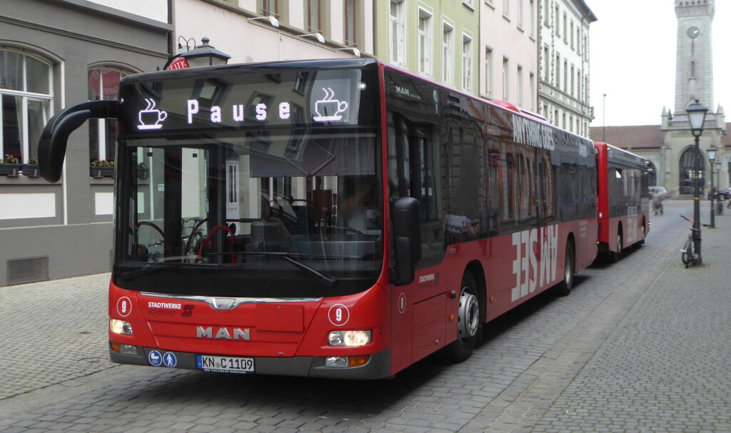 red and black bus with pause as destination