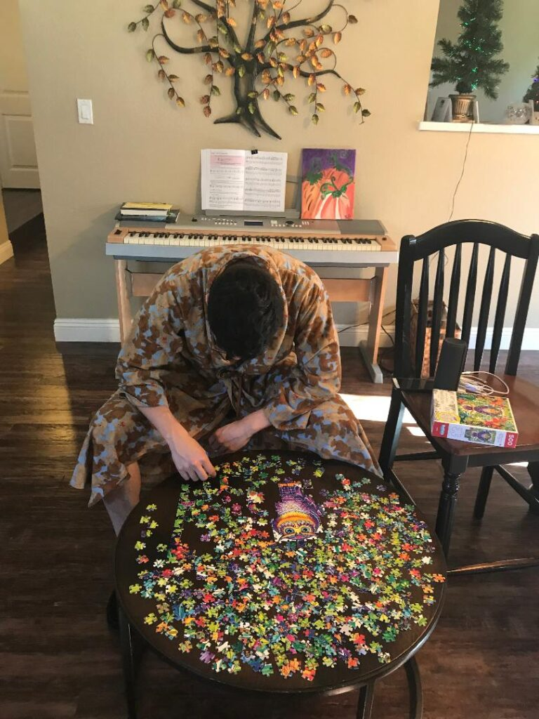 My 25 year old son, in a bear bathrobe, leaning over and working on a table.