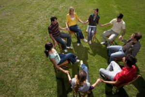 Support group sitting in chairs on the lawn showing they are getting help for emotional abuse.