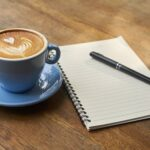 Pen and journal next to a cup of cappucino