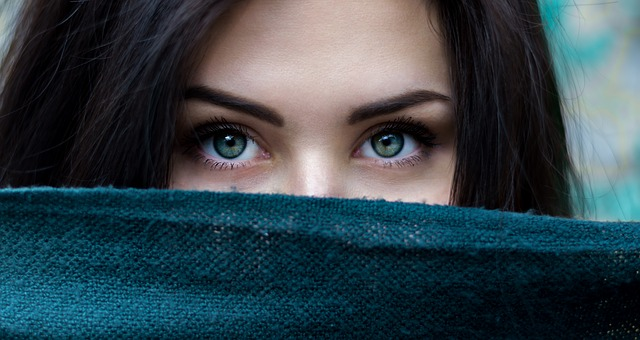 Pretty girl with blue eyes and auburn hair with a cloth covering the lower part of her face