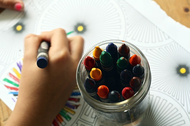 Little girls hand coloring a picture with a jar of crayons on the drawing.