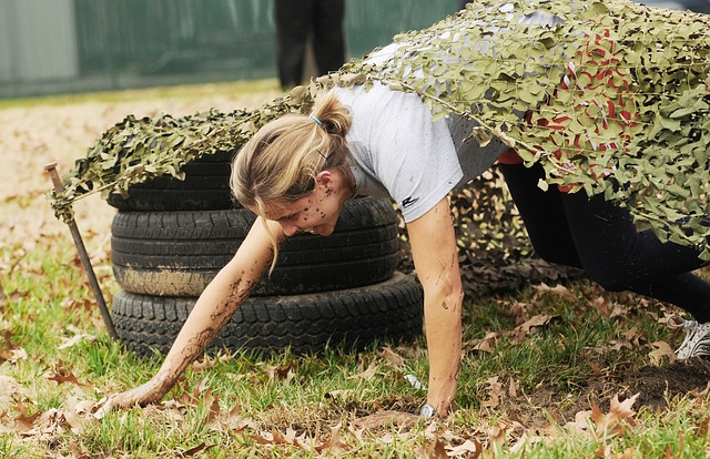 Woman in obstacle course climbing out from under a leave filled covering.
