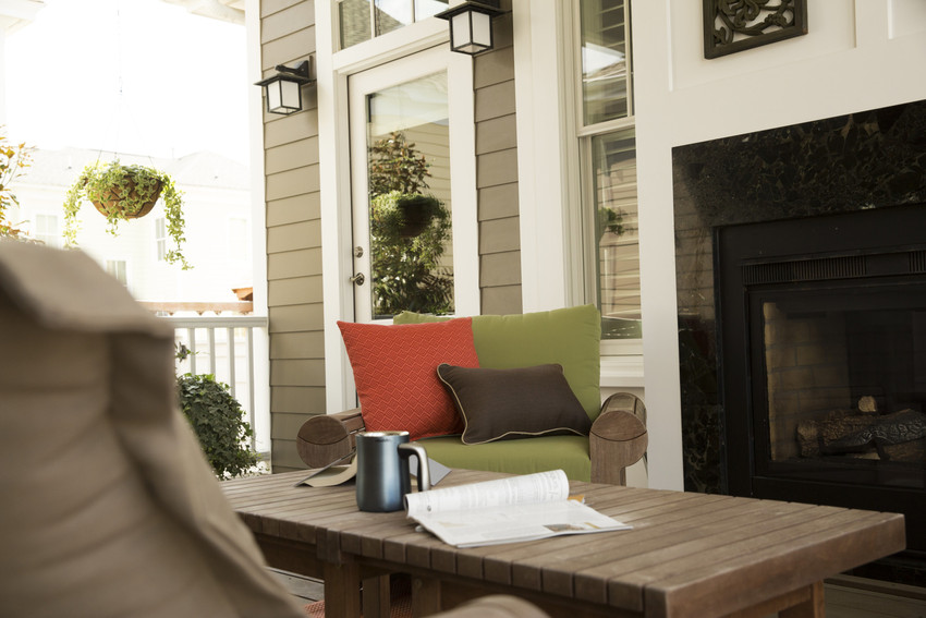 As you design your outdoor areas, try to create spaces that exude informal tranquility, too. This home is clad in HardiePlank lap siding in Timber Bark, and makes an ideal backdrop for this cozy porch space. The comfy furniture, the reading material, a warm cup of coffee, a fireplace and greenery—all ways to make a space feel friendly.