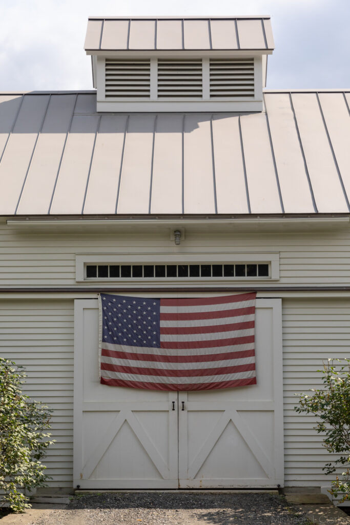The American Flag draped across the doors of a Woodstock Vermont barn.
