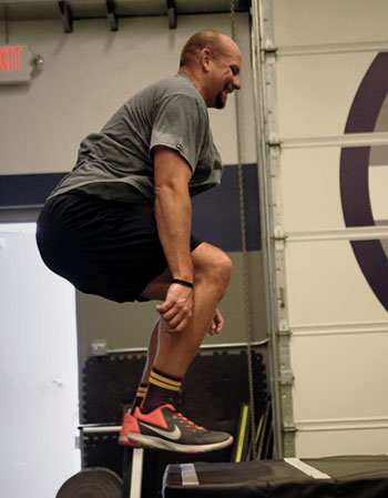 man exercising with box jump in gym
