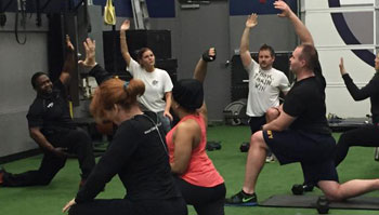 men and women working out with trainer