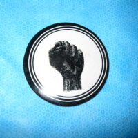 """An original """"protest"""" button from the 60's. Black clenched fist"""