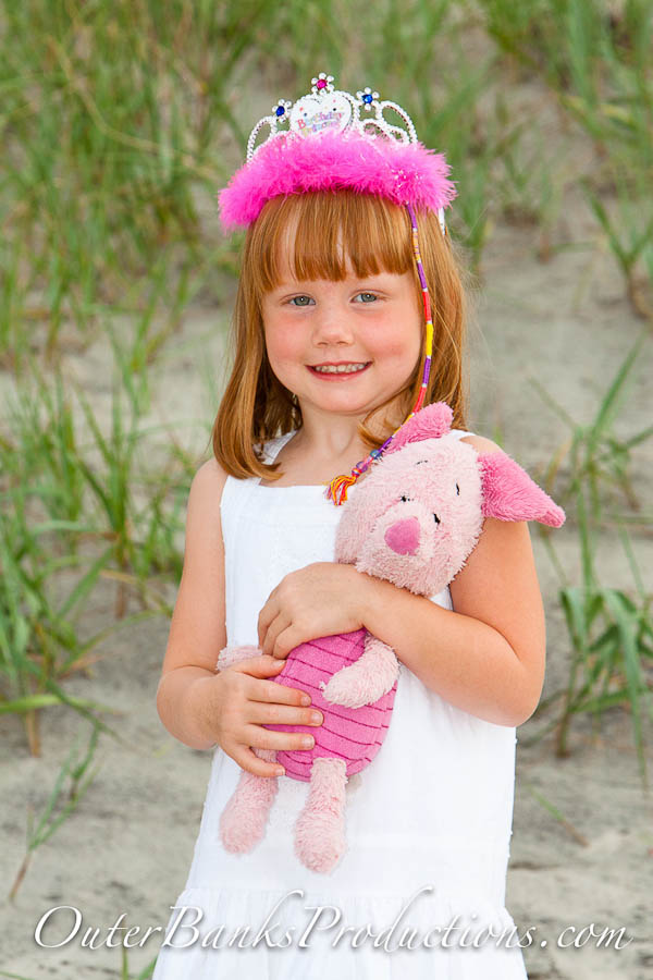 Young child portait with head ornament and stuffed animal.