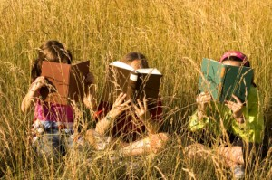 Kids reading in a field