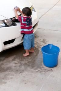 toddler boy using both hands to wash car