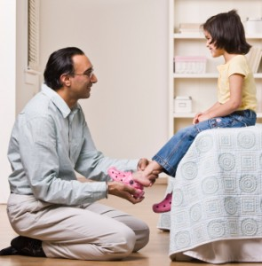 Father Helps Daughter Put On Shoes