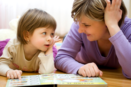 Mom And Young Daughter Pointing At Picture Book