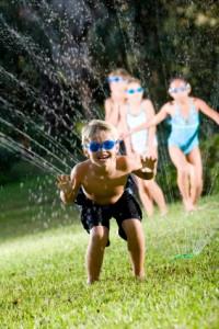 Happy Boy in Lawn Sprinkler With Friends