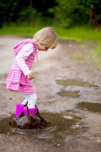 Young Girl Stepping In Mud Puddle