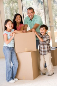 Family On Moving Day With Boxes