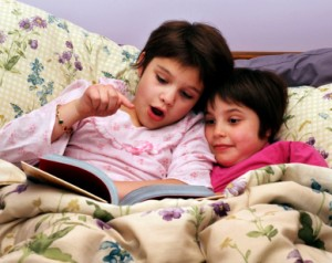 Young Sisters Reading To Each Other
