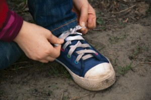 Child's hands tying shoe
