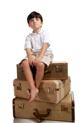 boy sitting on luggage