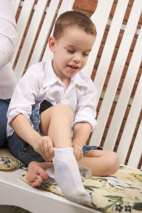 Boy putting on Sock