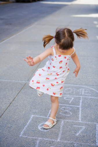 Little girl playing sidewalk chalk game