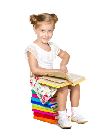 Little girl sitting on a pile of books