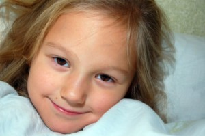 Portrait of little blonde brown-eyed girl in bed