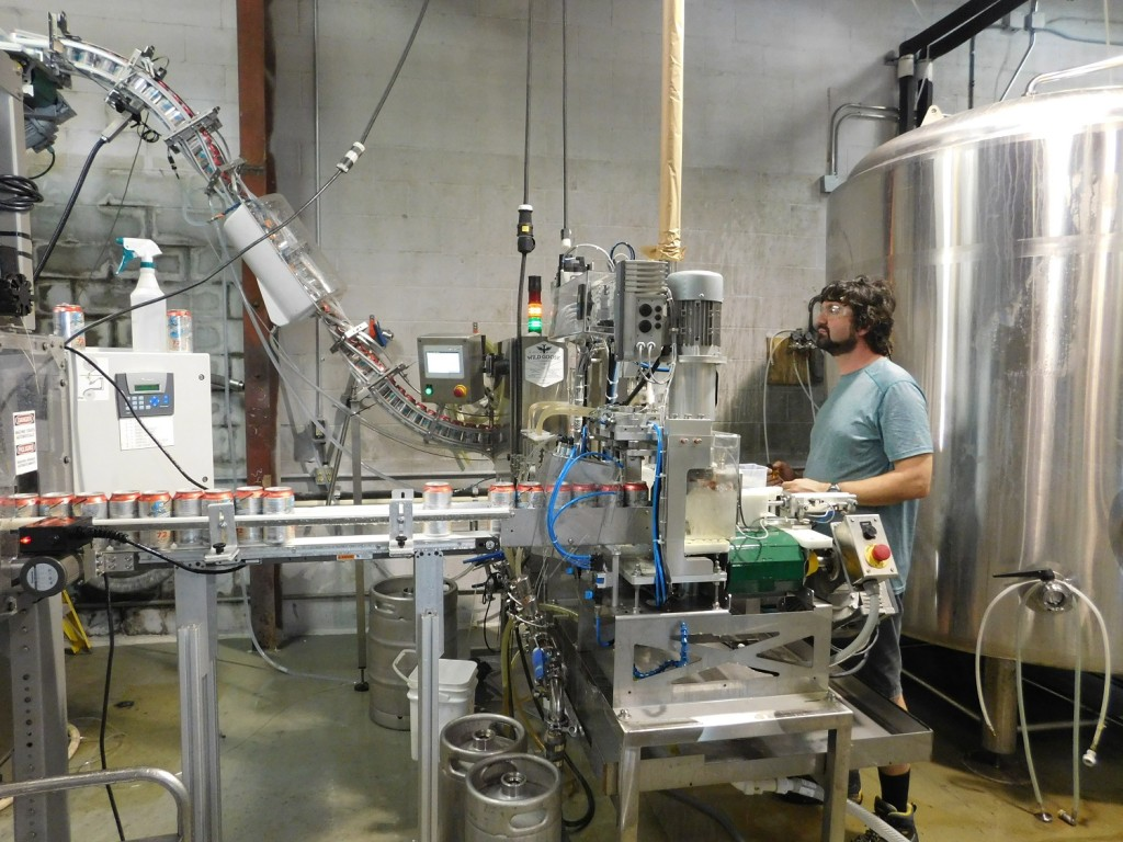 John Denny keeps an eye on his canning operation at First Magnitude Brewing Co.