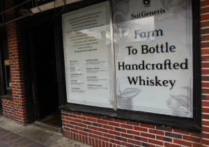 New signage on the front windows of the Fish Hawk Spirits Tasting Room promotes the companys Sui Generis whiskey brand.
