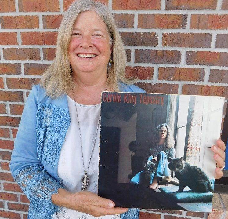"""Cathy DeWitt holds the """"Tapestry"""" album of her mentor Carole King. Photo by Gainesville Downtown)"""