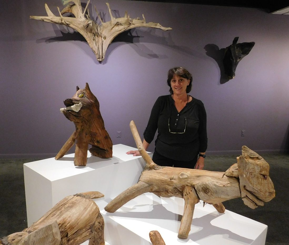 Curator Anne E. Gilroy stands among several wooden sculptures by Jesse Aaron in the Main Gallery of the Thomas Center. Photo by Gainesville Downtown)