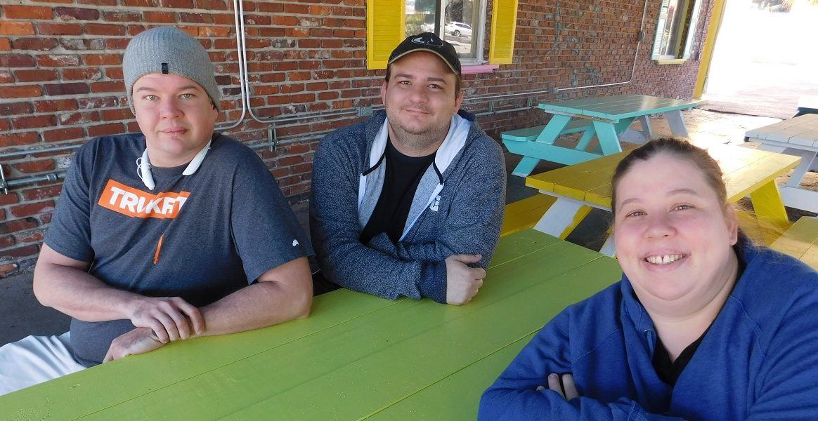 From left, Jacon Riesch, Tommy Newman and his wife, Shanti Riesch-Newman, are the co-owners of Piper Gis. Photo by Gainesville Downtown)