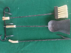 Hand forged fireplace tools with antler handle, including broom, dustpan, and fire poker
